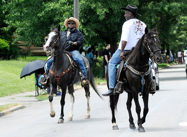 Don Knight | The Herald Bulletin<br /> A cowboy rides backwards on his horse during the Anderson Black Expo parade on Saturday.