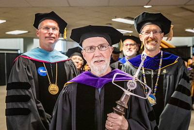 A. David McGuire, professor emeritus of ecology, carries the University of Alaska mace as grand marshal of the UA Fairbanks commencement ceremony Saturday, May 4, 2019, at the Carlson Center. Behind him, from left, are UA President Jim Johnsen, UA regents Karen Perdue and John Davies, and UAF Chancellor Daniel M. White.