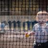 Ayden Blatt takes a peek through the tennis nets.