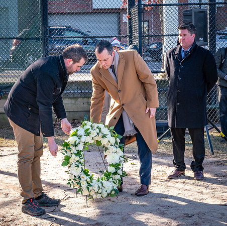 Boston Archeologist Joe Bagley (left), State Rep. Aaron Michlewitz and Boston Parks Commissioner Chris Cook (right) lay a wreath at the molasses tank site at Langone Park