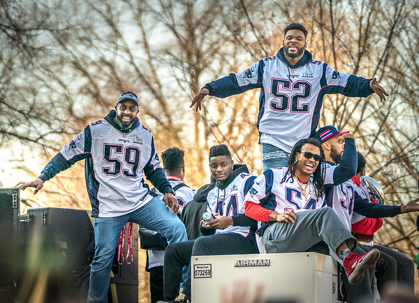 Pats players cheer from the duck boats wth fans at the rolling rally
