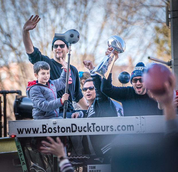 Tom Brady and his son wave to the crowd from a duck boat