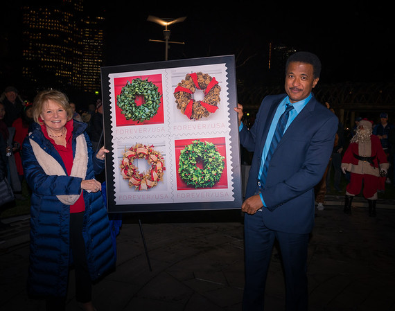 Acting Postmaster of Boston, Leroy Middleton, Jr., unveil the new US Postal Service holiday stamp with FOCCP President Joanne Hayes Rines