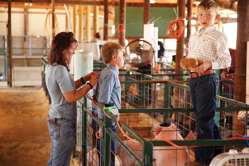 Matthew Gaston | The Sheridan Press <br /> Jonalee Watkins pins her son TJ's number to his shirt while her younger son Ty moves from one pen to the next to brush his pig at the Sheridan County Fair Thursday, July 30, 2020.