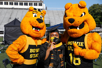 Bowie State University graduate Taleka Dalton, a cheerleader, with mascots Goldie, left, and Butch, during the Spring 2021 commencement, Friday, May 21, 2021.