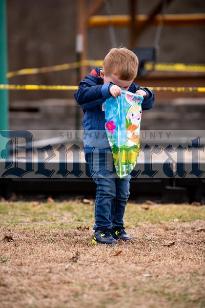 Three-year-old Kaeden Jasper peeks at his goodies.