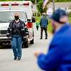 Diana Duffy joins the Upper Delaware Ambulance Corps on the parade route as a watcher claps.
