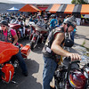 Record-Eagle/Keith King<br /> Eric Fischer, right, of Interlochen, and owner of Sleeping Bear Motor Sports, and his wife, Kris Fischer, left, get on their motorcycles at Classic Motor Sports Sunday, July 22, 2012 at the start of the 20th annual Ride for Father Fred to benefit the Father Fred Foundation. The event is sponsored by the Northern Chapter Harley Owners Group (HOG).
