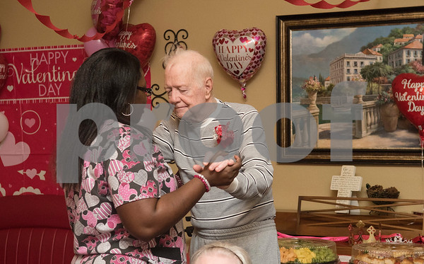 Health services assistant Astric Rogers dances with resident Darrell Bookman at the senior citizen's Valentine's Day prom held in the memory care unit at Prestige Estates Assisted Living and Memory Care in Tyler Tuesday Feb. 14, 2017. The event featured karaoke and snacks, and many residents wore formal dresses.  (Sarah A. Miller/Tyler Morning Telegraph)