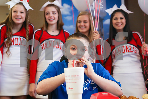 Ben Hall Hastings, 9, takes a bite of a french fry as Van High School cheerleaders stand behind him for a picture during lunch at Chick-Fil-A as part of a Make-A-Wish event for Ben in Tyler, Texas, on Saturday, Feb. 18, 2017. Ben's wish also involved a shopping spree at Game Stop and Best Buy. (Chelsea Purgahn/Tyler Morning Telegraph)