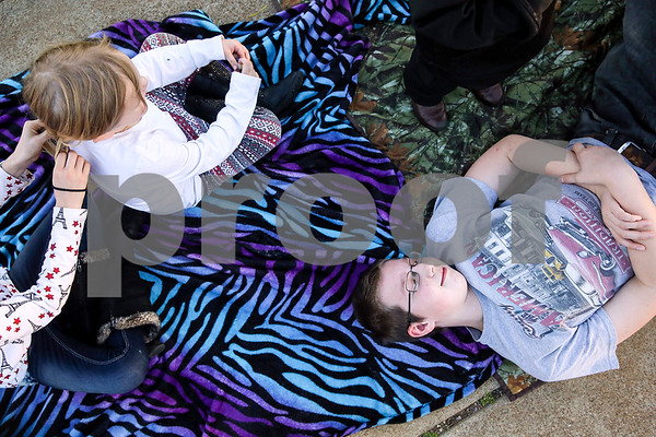 Dusty Walker, 11, braids Brandi Hursey's, 4, hair as Dakota Kennedy, 13, rests before Palestine's eighth annual Mardi Gras parade in Palestine, Texas, on Saturday, Feb. 18, 2017. Hundreds of people lined the streets to catch beads and watch floats, decorated cars and firetrucks drive along the parade route. (Chelsea Purgahn/Tyler Morning Telegraph)
