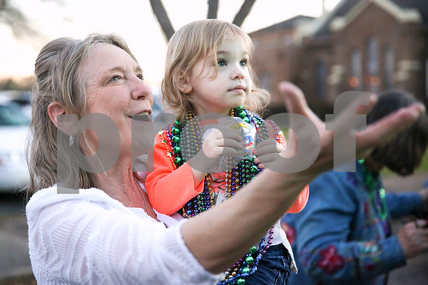 Rhonda Herrington reaches out her hand to catch beads as she holds her granddaughter Lauren Davis, 2, during Palestine's eighth annual Mardi Gras parade in Palestine, Texas, on Saturday, Feb. 18, 2017. Hundreds of people lined the streets to catch beads and watch floats, decorated cars and firetrucks drive along the parade route. (Chelsea Purgahn/Tyler Morning Telegraph)