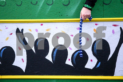 A parade participant prepares to throw beads during Palestine's eighth annual Mardi Gras parade in Palestine, Texas, on Saturday, Feb. 18, 2017. Hundreds of people lined the streets to catch beads and watch floats, decorated cars and firetrucks drive along the parade route. (Chelsea Purgahn/Tyler Morning Telegraph)