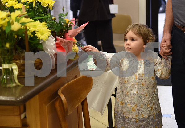 Tillie Showen, 4, leaves a flower at the East Texas Islamic Society in Tyler Thursday Feb. 2, 2017. The gathering of East Texans of various faiths was in response to a private Facebook event called Support Our Muslim Neighbors. The event page asked people to bring yellow flowers and greeting cards to the mosque as a sign of friendship.   (Sarah A. Miller/Tyler Morning Telegraph)