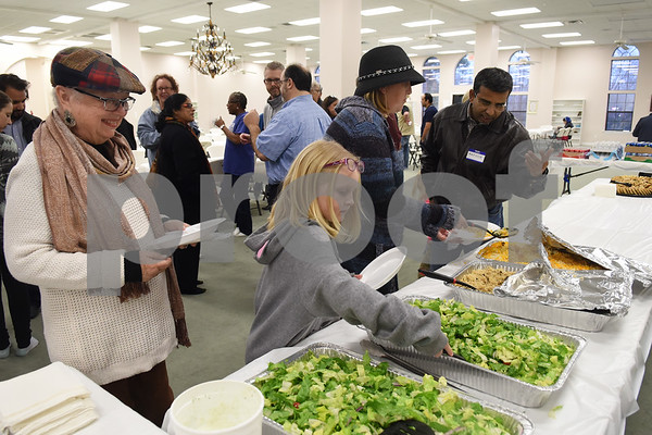 Mafooz Imam, far right, helps Yvonne Thrash, left, Qarayah Vick, 6, center, and Jenn Vick through the dinner line at the East Texas Islamic Society in Tyler Thursday Feb. 2, 2017. The gathering of East Texans of various faiths was in response to a private Facebook event called Support Our Muslim Neighbors. The event page asked people to bring yellow flowers and greeting cards to the mosque as a sign of friendship.   (Sarah A. Miller/Tyler Morning Telegraph)