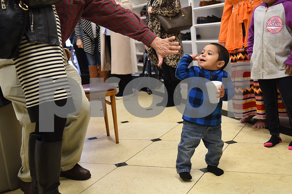 Noah Calderon, 1, gets a high five from Bill Farnum at the East Texas Islamic Society in Tyler Thursday Feb. 2, 2017. The gathering of East Texans of various faiths was in response to a private Facebook event called Support Our Muslim Neighbors. The event page asked people to bring yellow flowers and greeting cards to the mosque as a sign of friendship.   (Sarah A. Miller/Tyler Morning Telegraph)