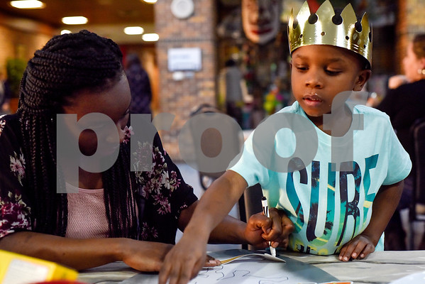 "Rahmeesha Marshall traces a paper arrow as Darrius Evans, 5, reaches for another paper arrow during the Mother-Son Date ""Knight"" at the Tyler Rose Garden Center in Tyler, Texas, on Friday, Feb. 23, 2018. Families enjoyed a Chick-fil-A dinner made crafts as they watched knights battle. (Chelsea Purgahn/Tyler Morning Telegraph)"