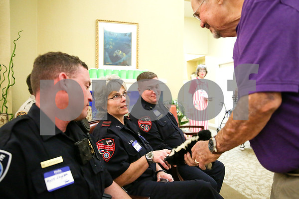 Chandler police officer Carla Moss looks up as she listens to Jene Carroll speak as he shows her a stuffed animal during an event co-hosted by the Rosy Nose Clown Alley and Atria Senior Living Community at the Atria Copeland in Tyler, Texas, on Monday, Feb. 27, 2017. The event honored law enforcement from around the Tyler area. (Chelsea Purgahn/Tyler Morning Telegraph)