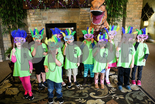 Stepping Stone School students pose for a picture during a Mardi Gras celebration at Prestige Estates in Tyler, Texas, on Tuesday, Feb. 28, 2017. Stepping Stone School students paraded down the halls of the assisted living facility and handed out beads to the residents. (Chelsea Purgahn/Tyler Morning Telegraph)