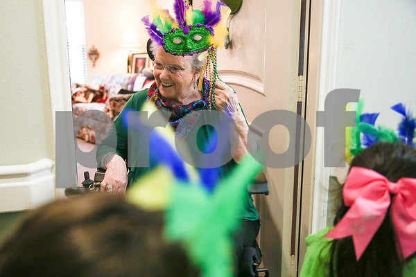 Kathryn McNeese smiles as children pass by during a Mardi Gras celebration at Prestige Estates in Tyler, Texas, on Tuesday, Feb. 28, 2017. Stepping Stone School students paraded down the halls of the assisted living facility and handed out beads to the residents. (Chelsea Purgahn/Tyler Morning Telegraph)