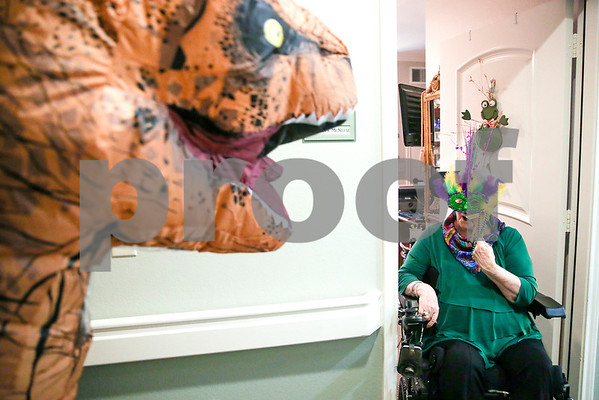 Kathryn McNeese sits in her doorway and looks at a person dressed as a T-Rex walking down the hallway during a Mardi Gras celebration at Prestige Estates in Tyler, Texas, on Tuesday, Feb. 28, 2017. Stepping Stone School students paraded down the halls of the assisted living facility and handed out beads to the residents. (Chelsea Purgahn/Tyler Morning Telegraph)