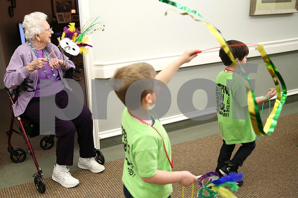 Anna Robinson smiles as children walk through the hallway during a Mardi Gras celebration at Prestige Estates in Tyler, Texas, on Tuesday, Feb. 28, 2017. Stepping Stone School students paraded down the halls of the assisted living facility and handed out beads to the residents. (Chelsea Purgahn/Tyler Morning Telegraph)