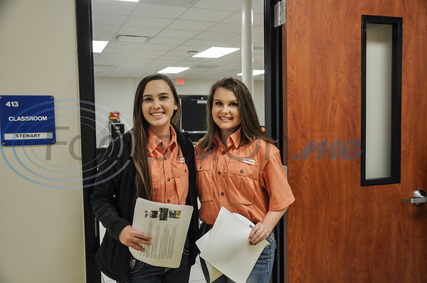 Jacksonville High School students Alexis King (left) and Lexi Counahan (right) pass out maps of the building during the high school's Open House for their new Career & Technology Building on Thursday, February 7.  (Jessica T. Payne/Tyler Morning Telegraph)