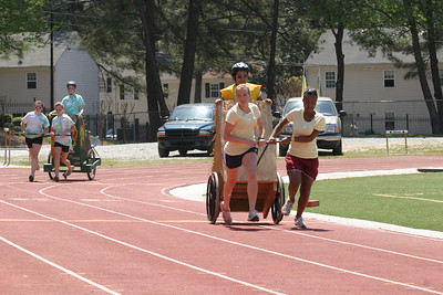 "In the second chariot race the gold faction (""The Golden Girls"") faced off against the green faction (""The Green Mean Fighting Machine"").  The gold faction, in front, of Lilly Sullivan, left, and Danielle Neal, pulling, and Diana Destin, driving, was victorious."