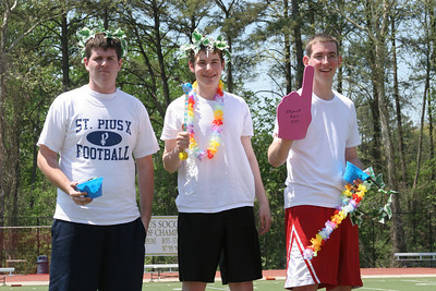 White faction members (l-r) Patrick Grace, John Jackson and Michael Dunn, winners of the St. Pius X chariot race, stand atop the winners' podium.