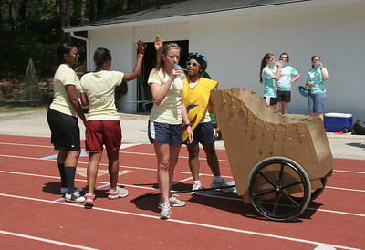 "The gold faction (""The Golden Girls"") of (foreground, l-r) Mikela Gordon, Danielle Neal, Lilly Sullivan and Diana Destin celebrates its victory over the green faction (""The Green Mean Fighting Machine"") following the second heat of Chariot Race 2010."