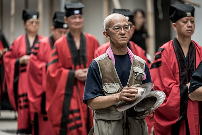 A man accompanies Taoist priests on their procession for the 30 Houses' Yulan Festival in SOHO on September 3, 2018.