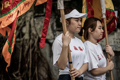 Two girls carry flags for the procession of Taoist priests as part of the 30 Houses' Yulan Festival in SOHO on September 3, 2018.