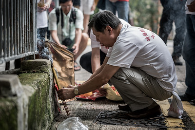 A man makes an offering at a local altar for the 30 Houses' Yulan Festival in SOHO on September 3, 2018.