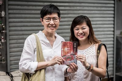 Katty Law (left) and Cardin Chan (right) display the promotional brochure they co-wrote. This bilingual publication aims to educate the public about the 30 Houses' Yulan Festival in SOHO on September 3, 2018.