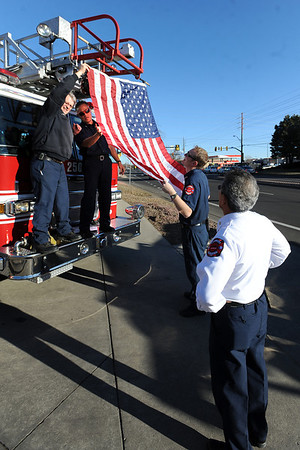 """Jay Ruggeri, left,  Tilio Lolotai and Dan Heisick, put up a flag on a fire truck before the service.<br /> It has been 30-years since William Duran and Scott Smith died in a fire training exercise in Boulder. Friends and family gathered at Station No. 3 in Boulder  to remember the sacrifice.<br /> For a video and photos from the ceremony, go to  <a href=""""http://www.dailycamera.com"""">http://www.dailycamera.com</a>.<br /> January 26, 2012 / Cliff Grassmick"""