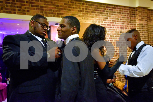 People adjust their outfits during Texas College's ninth annual Legacy Scholarship Fundraiser at Harvey Hall Convention Center in Tyler, Texas, on Friday, March 10, 2017. Five members of the community were honored for their commitment, dedication and service to Texas College and the City of Tyler. (Chelsea Purgahn/Tyler Morning Telegraph)