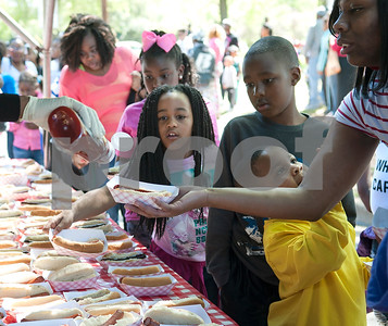 Children and their parents pass through the hot dog line at the 5th annual Easter egg hunt hosted by the JAABS Good Friday Committee at Emmett Scott Park in Tyler Friday March 25, 2016. Event organizer Ambra Phillips estimates that 1,000 children attended the event which included free food, bounce houses, faceprinting and music from local disc jockeys.   (Sarah A. Miller/Tyler Morning Telegraph)