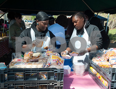 Volunteers Lecedra Johnson and Shakinya Sewell, members of Jazzy Jewels Social Club, help serve lunch at the 5th annual Easter egg hunt hosted by the JAABS Good Friday Committee at Emmett Scott Park in Tyler Friday March 25, 2016. Event organizer Ambra Phillips estimates that 1,000 children attended the event which included free food, bounce houses, faceprinting and music from local disc jockeys.   (Sarah A. Miller/Tyler Morning Telegraph)