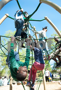 Londyn Matlock, 8, of Tyler, hangs from playground equipment at the 5th annual Easter egg hunt hosted by the JAABS Good Friday Committee at Emmett Scott Park in Tyler Friday March 25, 2016. Event organizer Ambra Phillips estimates that 1,000 children attended the event which included free food, bounce houses, faceprinting and music from local disc jockeys.   (Sarah A. Miller/Tyler Morning Telegraph)