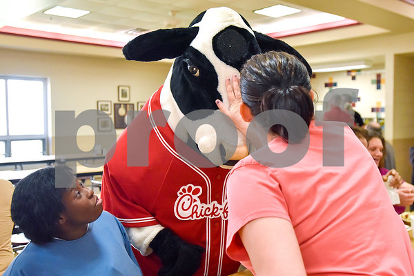 Whitney McCoy looks at the Chick-fil-A cow as Christina Benek pets his head at the Salvation Army in Tyler, Texas, on Monday, March 20, 2017. The Chick-fil-A locations on Broadway Avenue and Troup Highway worked together on a soup drive and raised a total of 5,116 bowls of soup to donate to the Salvation Army. (Chelsea Purgahn/Tyler Morning Telegraph)