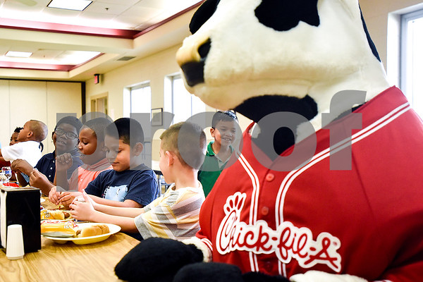A Chick-Fil-A cow sits with kids as they enjoy a meal as part of the Salvation Army after school program at the Salvation Army in Tyler, Texas, on Monday, March 20, 2017. The Chick-fil-A locations on Broadway Avenue and Troup Highway worked together on a soup drive and raised a total of 5,116 bowls of soup to donate to the Salvation Army. (Chelsea Purgahn/Tyler Morning Telegraph)