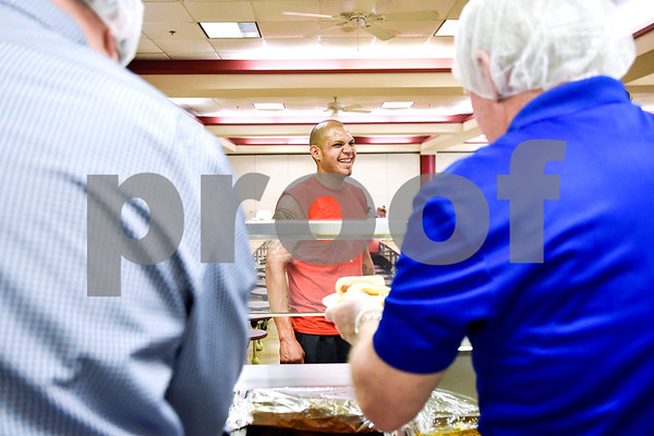A man smiles as Chick-fil-A employees prepare plates for dinner at the Salvation Army in Tyler, Texas, on Monday, March 20, 2017. The Chick-fil-A locations on Broadway Avenue and Troup Highway worked together on a soup drive and raised a total of 5,116 bowls of soup to donate to the Salvation Army. (Chelsea Purgahn/Tyler Morning Telegraph)