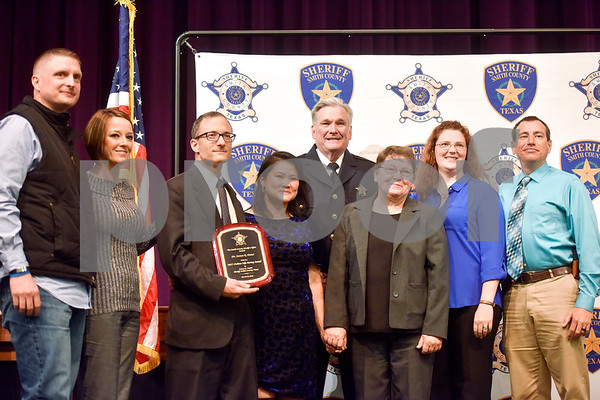 Dr. Steven R. Potter, third from left, stands with others after he was awarded the Civilian Life Saving Award at the annual Smith County Sheriff's Office Awards Dinner at Green Acres Baptist Church in Tyler, Texas, on Tuesday, March 20, 2018. This annual event gives Sheriff Larry Smith the opportunity to spotlight outstanding examples of leadership and excellence in the Sheriff's Office's employees. (Chelsea Purgahn/Tyler Morning Telegraph)