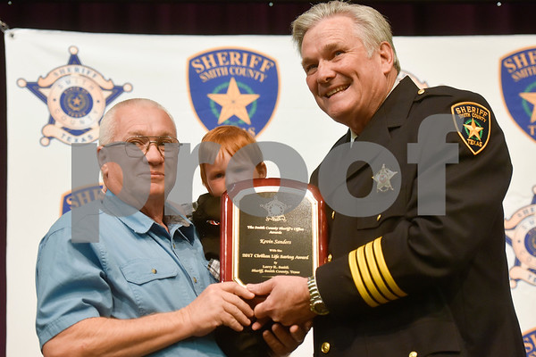 Kevin Sanders holds a young child as he is awarded the Civilian Life Saving Award by Sheriff Larry Smith at the annual Smith County Sheriff's Office Awards Dinner at Green Acres Baptist Church in Tyler, Texas, on Tuesday, March 20, 2018. This annual event gives Sheriff Larry Smith the opportunity to spotlight outstanding examples of leadership and excellence in the Sheriff's Office's employees. (Chelsea Purgahn/Tyler Morning Telegraph)