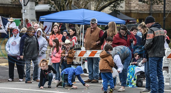 Children collect candy thrown during the inaugural Rusk Mardi Gras Parade on Saturday, March 2. The event was hosted by the Chamber and included a King Cake competition, car show, live music, bounce house , face painting and more. (Jessica T. Payne/Tyler Morning Telegraph)