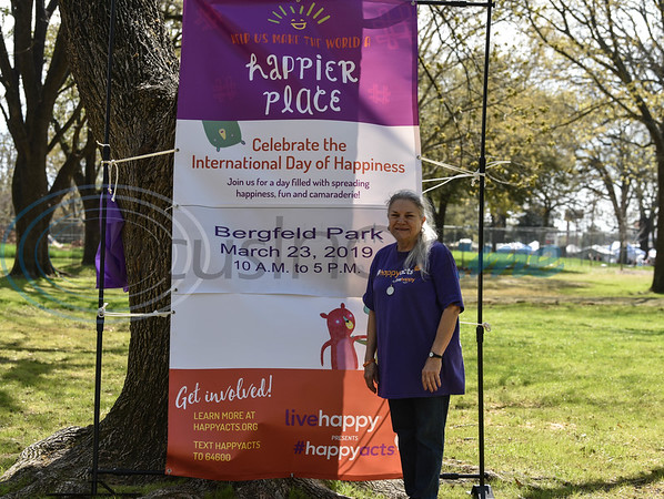 Tyler Happy Wall Captain Connie Harmon stands next to the event banner as part of the 6th annual International Day of Happiness and was held at Bergfeld Park on Saturday, March 23. (Jessica T. Payne/Tyler Morning Telegraph)