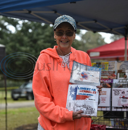 Festival vendor and author Lurlene Bowden holds up her books at the Hogg Fest in Rusk on Saturday, March 23. The Rusk Chamber of Commerce hosted the first-ever event which included several contests, a petting zoo, live entertainment and food vendors. (Jessica T. Payne/Tyler Morning Telegraph)