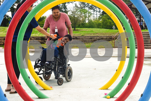 A woman hands Jon'Arian Brown an egg as Shabrandon Lowd pushes his wheelchair during an Easter egg hunt at the Boys and Girls Club of East Texas in Tyler, Texas, on Thursday, March 29, 2018. (Chelsea Purgahn/Tyler Morning Telegraph)