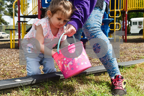 Dixie Matthews, 4, puts an egg into a basket held by Melissa Miller during an Easter egg hunt at the Boys and Girls Club of East Texas in Tyler, Texas, on Thursday, March 29, 2018. (Chelsea Purgahn/Tyler Morning Telegraph)