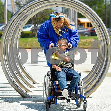 Carlton Thirkill laughs as Brandy Starks pushes him through a tunnel in his wheelchair during an Easter egg hunt at the Boys and Girls Club of East Texas in Tyler, Texas, on Thursday, March 29, 2018. (Chelsea Purgahn/Tyler Morning Telegraph)
